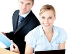 Ambitious couple of businesspeople using a lapop and reading a d — Stock Photo