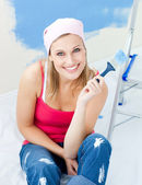 Joyful young woman holding a paint brush smiling at the camera — Stock Photo