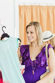 Caucasian blond woman looking at a shirt in a clothes store — Stock Photo