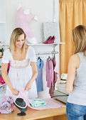 Positive saleswoman packing clothes in a bag — Stock Photo