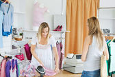 Friendly saleswoman packing clothes in a bag — Stock Photo