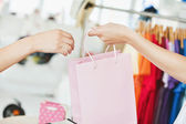A saleswoman giving a shopping bag to a customer — Stock Photo
