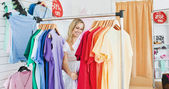 Merry blond woman choosing colorful clothes — Stock Photo