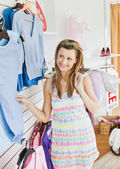 Cute young woman choosing clothes in a shop — Stock Photo