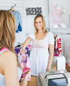 Smiling saleswoman giving clothes to a female customer — Stock Photo