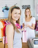 Zachwycony kobieta biorąc torba na zakupy z ekspedientka — Zdjęcie stockowe