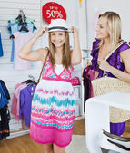 Laughing woman trying a hat with her friend — Stock Photo