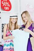 Blij vrienden kijken naar een shirt in een kleding winkel — Stockfoto