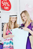 Delighted friends looking at a shirt in a clothes store — Stok fotoğraf