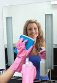 Smiling woman cleaning a mirror in a bathroom — Stock Photo