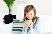 Relaxed businesswoman enjoying her coffee sitting on a sofa — Stock Photo
