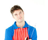 Thougtful young cook holding a cookware — Stock Photo