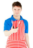 Handsome young cook holding a cookware — Stock Photo