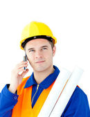 Ambitious male architect talking on phone holding blueprints — Stock Photo