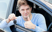 Positive young man holding a key sitting in a car — Stock Photo