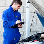 Handsome mechanic writing on a clipboard — Stock Photo
