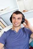 Lively young man listening to music sitting on the couch — Stock Photo