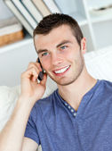 Charismatic young man talking on phone sitting on the sofa — Stock Photo