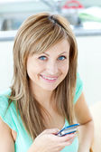 Happy young woman sending a text smiling at the camera — Stock Photo