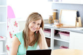 Joyful blond woman using her laptop smiling at the camera — Стоковое фото