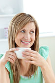 Charming caucasian woman holding a cup of coffee sitting in the — Stock Photo
