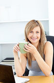 Attractive businesswoman holding a cup using her laptop — Stock Photo