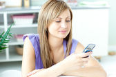 Concentrated blond woman sending a text sititng on a sofa — 图库照片