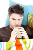 Ill depressed man holding a cup of coffee lying on the sofa — Stock Photo