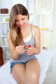 Glowing young woman varnishing her nails with red nail polish — Stock Photo