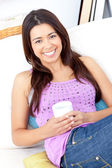 Bright woman holding a cup of coffee smiling at the camera — Stock Photo