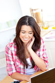 Glowing asian woman using her laptop sitting sitting in the kitc — Stock Photo
