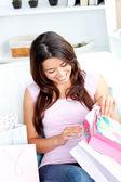 Joyful asian woman with shopping bags on the sofa — Stock Photo