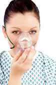 Diseased young woman with an oxygen mask looking at the camera — Stock Photo