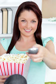 Cute caucasian woman holding a remote and popcorn looking at the — Stock Photo
