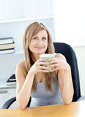 Relaxed woman holding a cup sitting on a chair at home — Stock Photo