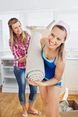 Enthusiastic women holding a carpet standing in the kitchen — Stock Photo