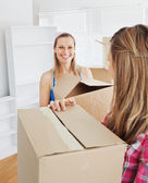 Two radiant female friends holding boxes after moving — Stock Photo