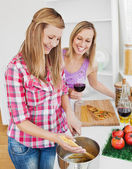 Delighted friends cooking spaghetties — Stock Photo