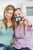 Close female friends taking pictures of themselves with a digital camera — Stock Photo