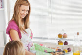 Positive young woman baking cookies for her girlfriend — Stock Photo