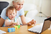 Positive family using laptop and playing with toys — Stock Photo