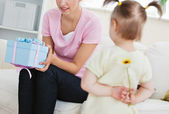 Surprised mother getting a present from her little daughter — Stock Photo