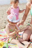 Sweet little girl using suncream at the beach — Stock Photo