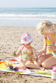 Little girl using suncream at the beach — Stock Photo
