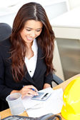 Ambitious businesswoman using her calculator — Stock Photo
