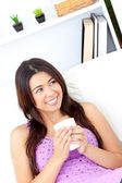 Positive asian woman holding a cup of coffee at home — Stock Photo