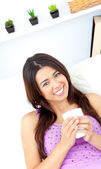 Pretty asian woman holding a cup of coffee at home — Stock Photo