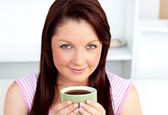 Portrait of an attractive woman holding a cup of coffee at home — Stock Photo