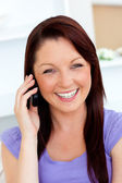 Laughing young woman talking on phone at home — Stock Photo