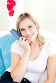 Captivating woman smiling at the camera holding a remote — Stock Photo